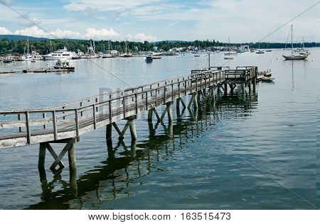 Long Pier:  A wooden walkway extends far across the shallow end of a bay in Maine.