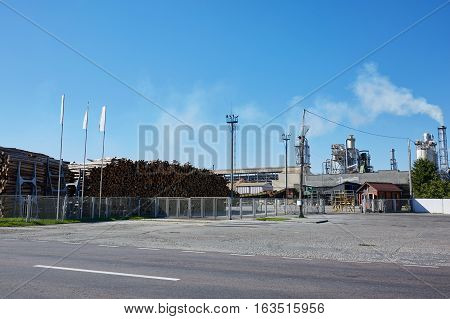 Wood factory with smoking chimneys. Woodchip production.
