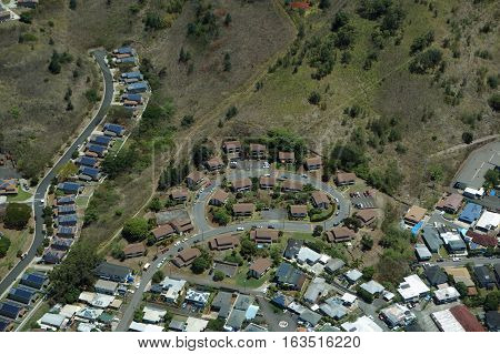 Aerial of luxury residential town with House many of which feature roof top solar on slopes of Mountain on Oahu Hawaii.