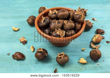 A photo of peeled and unpeeled roasted chestnuts in an earthenware bowl, on a vibrant teal blue background with copyspace