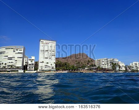 Wavy water on ocean off Kaimana Beach with Diamondhead hotels and condos on Oahu Hawaii.