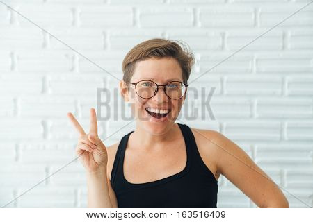 Happy girl with glasses and short hair posing at the camera smiling and showing a gesture hippie freedom and peace.