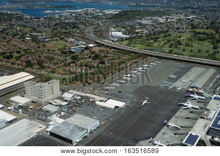 HONOLULU - APRIL 20: Aerial view of planes helicopters Golf Course Pearl Harbor Parking lots Roads leading into Airport and cars parked by buildings at the Honolulu International Airport HNL next to the water on Oahu Hawaii. April 20 2016.