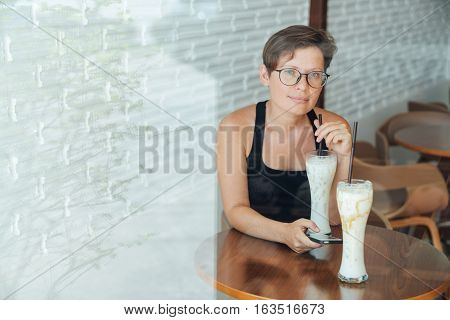Happy girl drinking milk with caramel and relaxing in cafe. Natural makeup and hairstyle. holding in his hand a smartphone