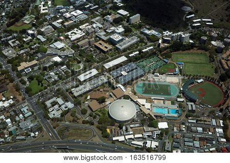 HONOLULU - APRIL 20 2016: Aerial view of Landmark University of Hawaii Baseball Les Murakami Stadium and Stan Sheriff Center in Manoa with H-1 Highway and Surrounding town community Honolulu Hawaii April 20 2016.