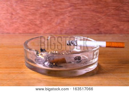 cigarettes in ash-tray isolated  on wooden background