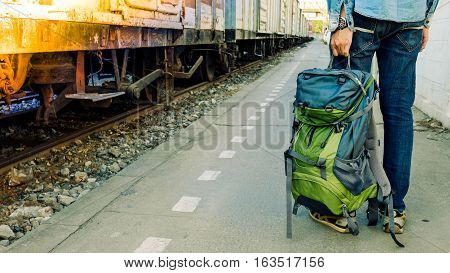 Backpacker Waiting For Long Gourney Travel At Train Station With Backpack. Travel Concept With Vinta