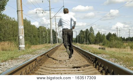 Man in a business dress suit runs and moves away along the rails on the railroad path. Business and society progress and pressure speed and stress concept.
