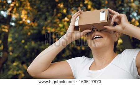 Woman explores virtual reality using cardboard VR glasses. Augmented reality quickly comes in human lives. VR mounted displays helmets and glasses are the most popular devices for playing AR games.