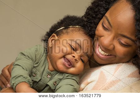 Happy African American mother and daughter playing.