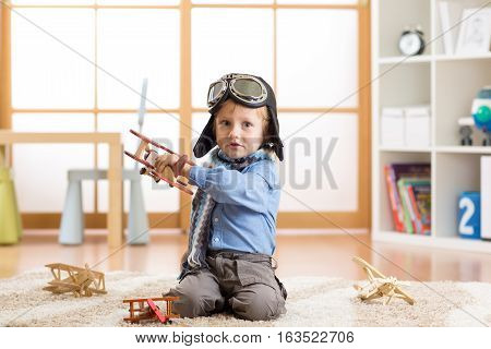 Cute baby dreaming of being pilot. Little child boy playing with toy airplanes