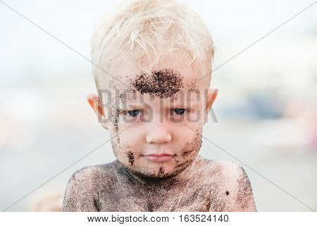 Funny photo of happy baby boy on beach with dirty face covered with black sand. Family travel healthy lifestyle recreation water outdoor activity on summer beach vacation with children