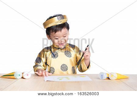 School asian boy in traditional dress Ao Dai learning with calligraphy at Vietnamese lunar New Year celebrating fair day organized.
