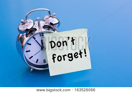 Dont Forget written on sticker with alarm clock on blue table