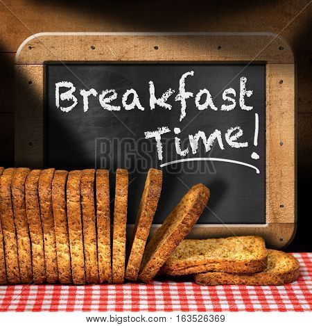 Rusks of wholemeal flour on a table with checkered tablecloth and a blackboard with text Breakfast time!