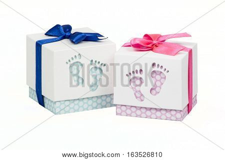 Two small boxes with gift for a newborn baby, pink and blue polka dots, top decorated with bow