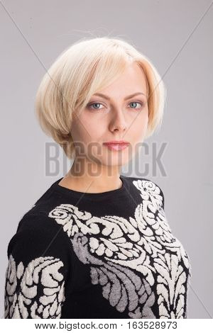 Portrait of blond lady with delicate and clear skin isolated on white background in studio. Model woman with perect hair cut looking at camera.