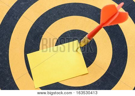 Red arrow hitting yellow blank note over in bullseye on dartboard background Business opportunities success concept