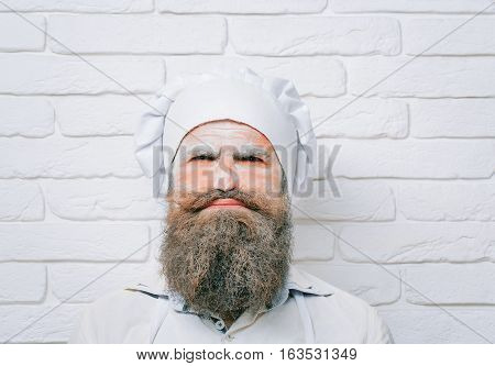 Handsome crazy man cook or baker with flour on face beard and moustache poses in chef uniform and hat on white brick wall
