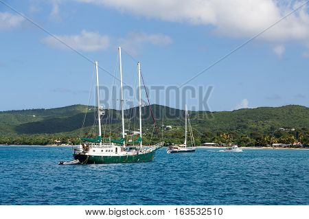 A three masted sailboat moored in a calm Caribbean harbor