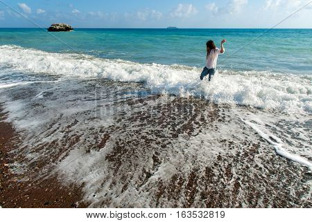 Young woman with long hair play waves running, feeling the sea, seascape beach