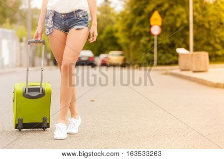Travel adventure teenage journey concept. Woman wearing denim shorts and white sneakers walking with green suitcase