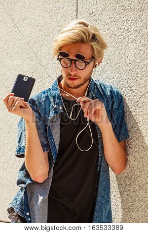 Men fashion technology urban style clothing concept. Hipster guy standing on city street wearing jeans outfit and eccentric sunglasses listening to music and holding phone