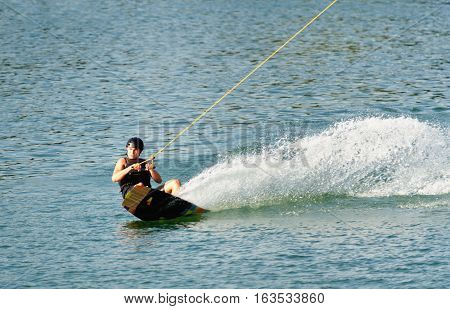 Sportsman enjoying on wakeboard, toned image, horizontal