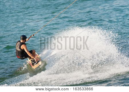 Young sportsman wakeboarding on lake, toned image,