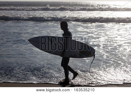 CONCON-JUNE 07 2015: Surfer go to the beach to spend a fun time in the water. Image is backlit and features the subject in silhouette in Concon Chile on June 7, 2015