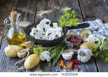 Mushrooms, parsley, dill, onion, olive oil, spices - ingredients for the preparation of mushroom dishes in a frying pan on a wooden background