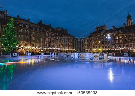 Warsaw, Poland - December 25th, 2016. Xmas tree and mermaid statue surrounded by historical buildings and festive decorations at the ski rink on the Old town square by Christmas night.
