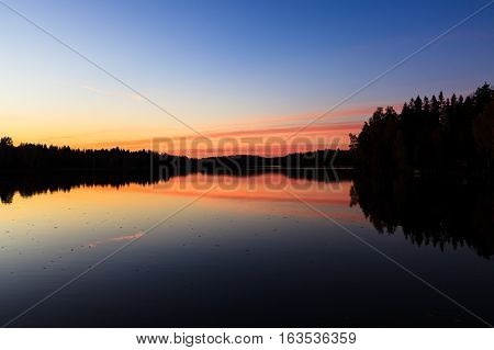 Serene view of calm lake and sunset clouds at twilight