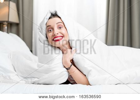 Portrait of young smiling woman hidding under the white sheets on the bed
