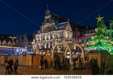 Ghent, Belgium - December 27th, 2016. Gent city winter festival in Flanders. Christmas fair with Xmas tree and festive decorations surrounded by historical buildings on the Ghent Old town square.