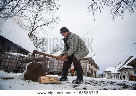 Breb Romania - November 16 2016: An elderly man slices wood logs on a winter day in Breb Maramures Romania.