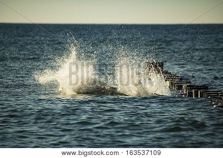 abstract splashing water in blue sea from a man leaped from the breakwater