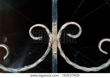 Close Up Of A Muddy Wrought Iron With Spider Web