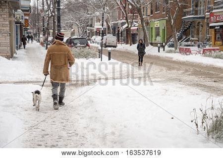 Montreal CA - 12 December 2016: Snowstorm in Montreal. Pedestrians on Laurier Avenue.