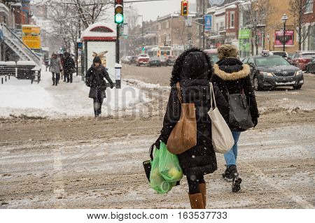 Montreal CA - 12 December 2016: Snowstorm in Montreal. Pedestrians in Mile End Neighbourhood