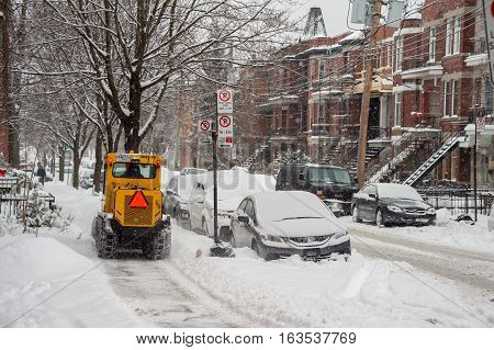 Montreal CA - 12 December 2016: A snowplow in motion in Mile End Neighbourhood during snow storm.
