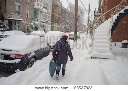 Montreal CA - 12 December 2016: Snowstorm in Montreal. Pedestrians in Plateau Neighbourhood