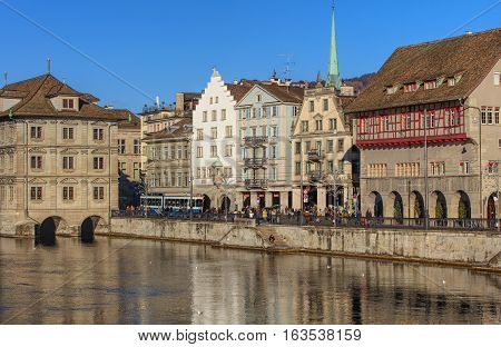 Zurich, Switzerland - 27 December, 2016: historic buildings along the Limmat, people on the embankment of the river. The leftmost building is the Zurich City Hall, housing the city and cantonal parliaments. Zurich is the largest city in Switzerland.