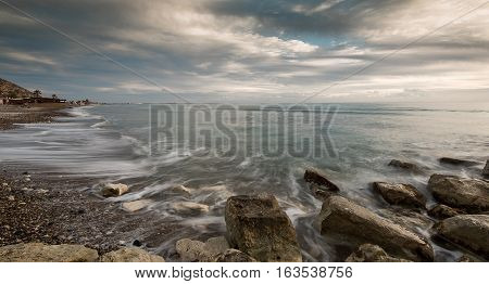Beautiful rocky coastline seascape with dramatic clouds late in the evening in Limassol Cyprus