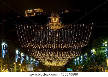 Christmas decorations and lighting on the street at evening view of the Bahai gardens from Sderot Ben Gurion in Haifa Israel