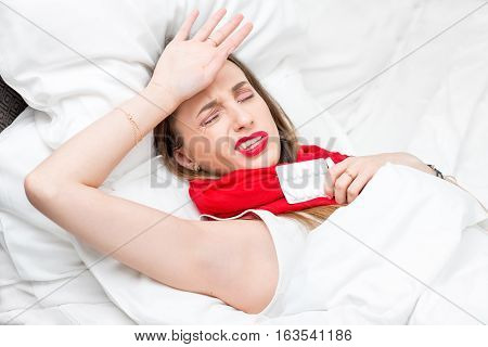 Young woman suffering from cold lying on the bed with red scarf and pills