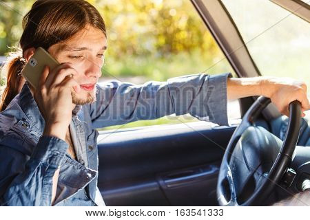 Talking while drive danger fresh driver concept. Young man driving car using his smartphone talking with someone.