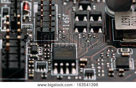 transistors capacitors resistors and other electronic components mounted on motherboard macro closeup.selective focus