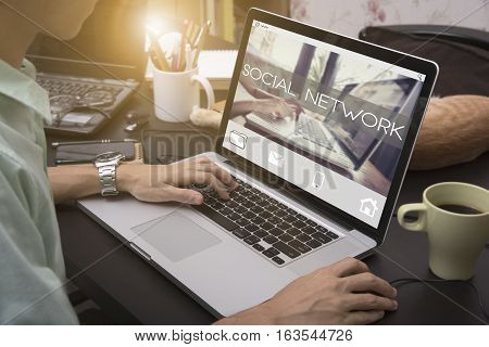 business hand typing on a laptop keyboard with Social network homepage on the computer screen communication networking online concept.