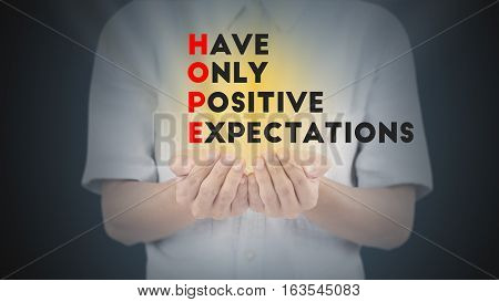 Hand with wording hope have only positive expectation and gold light.